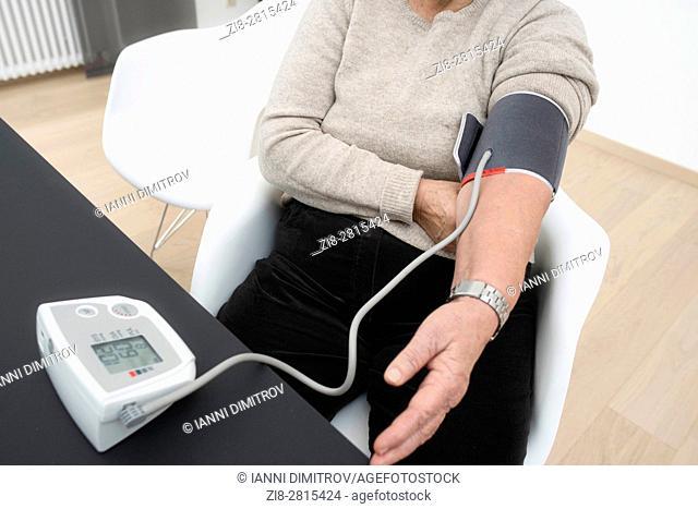 Senior woman checks her blood pressure