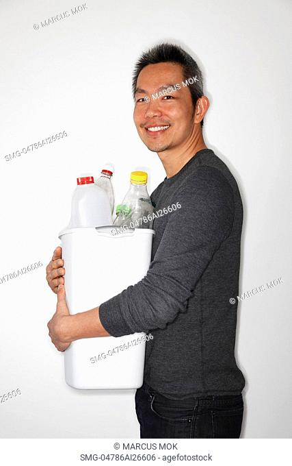 Chinese man holding bucket of bottles to recycle