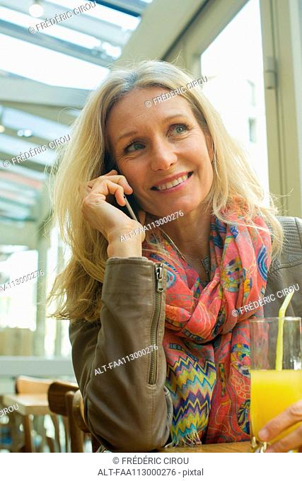 Mature woman talking on cell phone and smiling in cafe