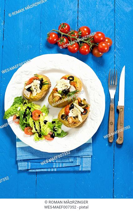 Mediterranean baked potatoes with tomatoes, spring onions, olives, chicken, ricotta and parmesan cheese