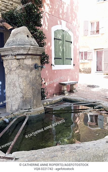 Traditional stone fountain and basin with clear rippling water, reflecting shutters in pastel shades on the pretty pink and cream sunlit buildings opposite in...
