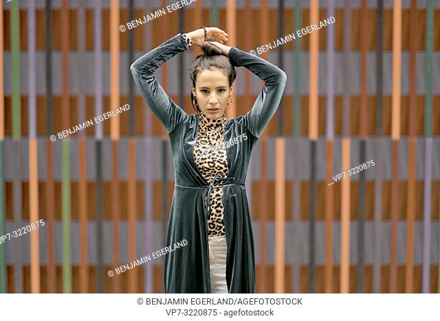 portrait of confident fashionable woman, in front of geometrical line pattern, in Munich, Germany