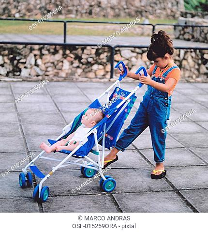 a girl pushing a baby cart with a baby