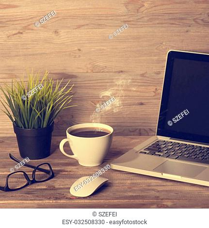 Wooden office table with laptop, cup of hot coffee, mouse, glasses and pot plant, in dramatic light vintage toned