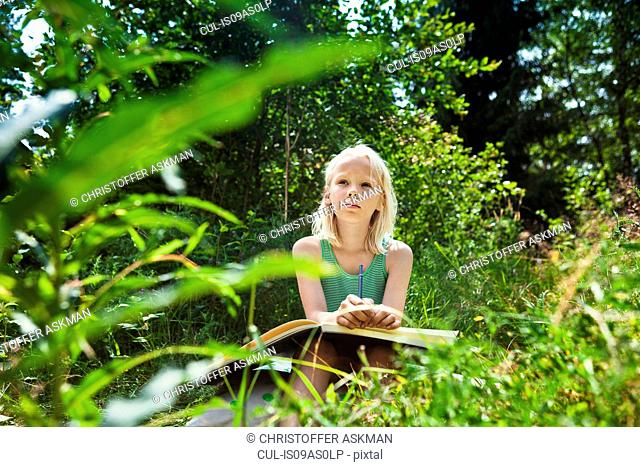 Young girl sitting in rural environment with sketchbook