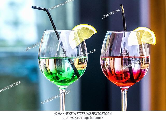 Two cocktail glasses with lime and straws