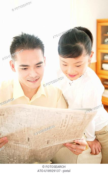Father and child reading a newspaper