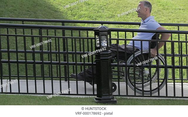 Man with spinal cord injury in a wheelchair using accessible wheelchair ramp uphill and turning corner