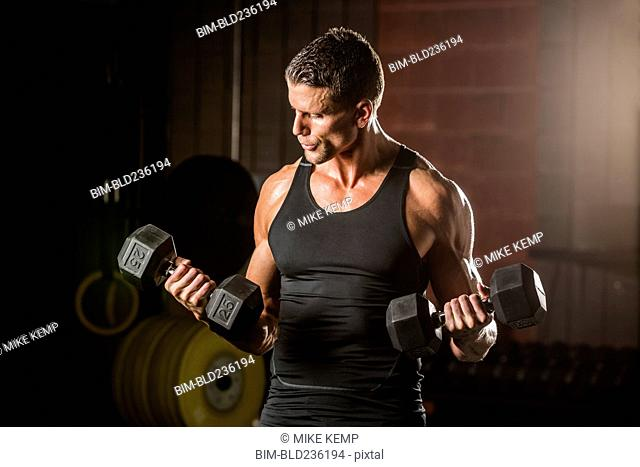 Caucasian man lifting dumbbells in gymnasium