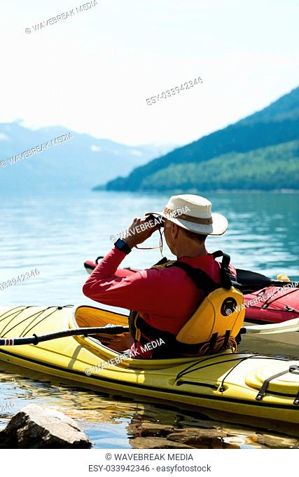 Man using binoculars while sitting in kayak