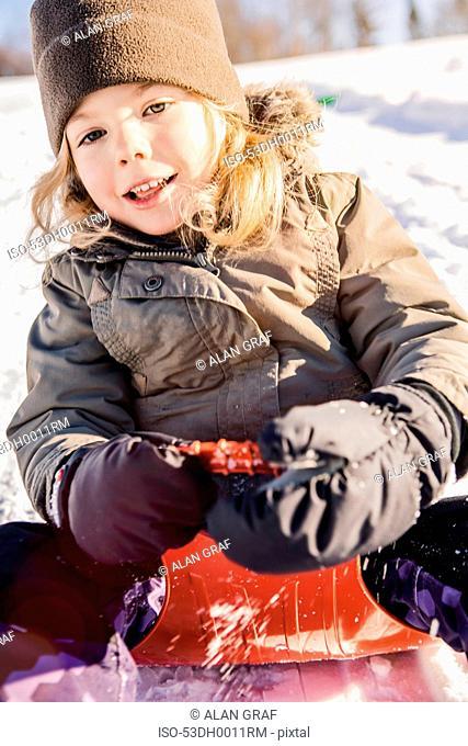Smiling girl sledding in snow