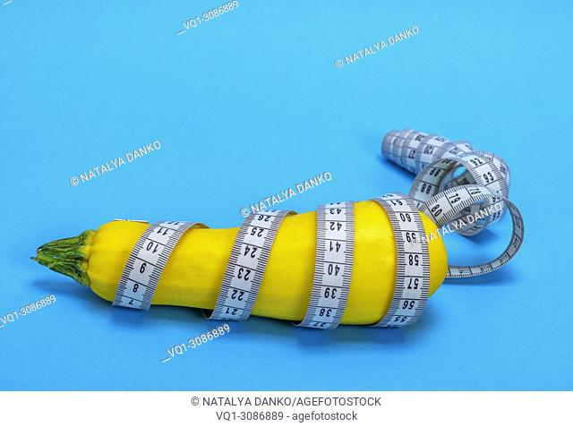 yellow raw zucchini wrapped in a measuring tape on a blue background, concept of losing weight and healthy lifestyle