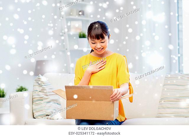 people, delivery, commerce, shipping and shopping concept - happy asian young woman with cardboard parcel box at home over snow