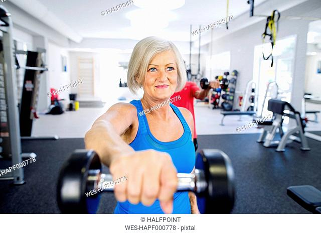 Mature woman working out in fitness gym