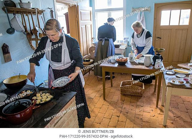 Veronika Rehhagen (r) and Karola Beckmann (l) prepare food at the historical farm kitchen of the Advent market 'Wintersonnenwerke'(lit