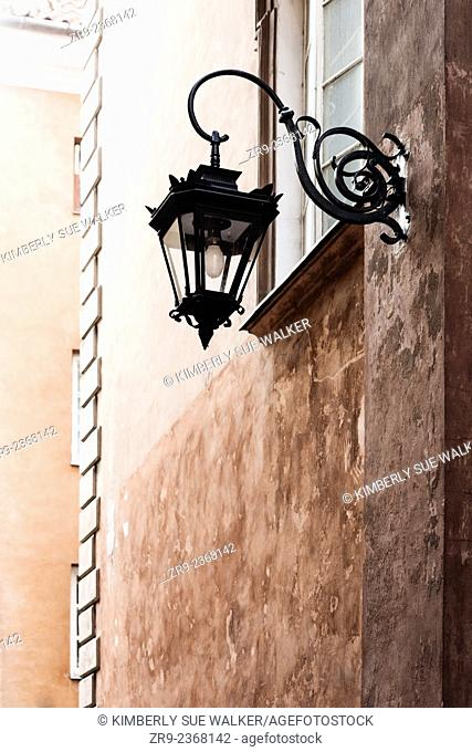 Lamp post on wall exterior in Rynek Starego Miasta, the historic Old Town that was extensively rebuilt in 1953 after WW2, Warsaw, Poland, Europe