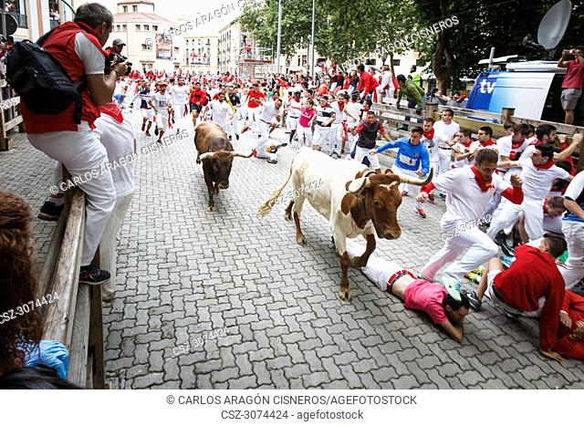 PAMPLONA, SPAIN - JULY 14, 2017: Bulls and people running on the street, encierro, in the festival of San Fermin. Bulls of Eduardo Miura in the eighth and last...