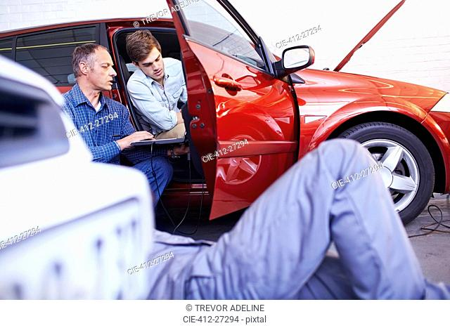 Mechanics with laptop talking at car in auto repair shop