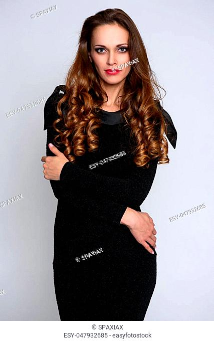 Beautiful confident young woman with long curly hair wearing the elegant black dress. Isolated