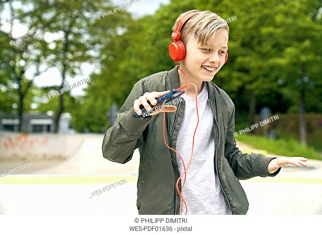Boy with headphone dancing while listing to music on smartphone