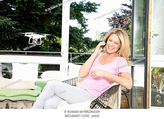 Woman talking on the phone unaware of drone in background
