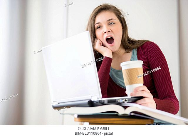 Hispanic girl yawning at desk