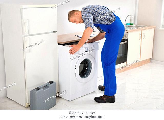 Young Man In Overall Repairing Washing Machine