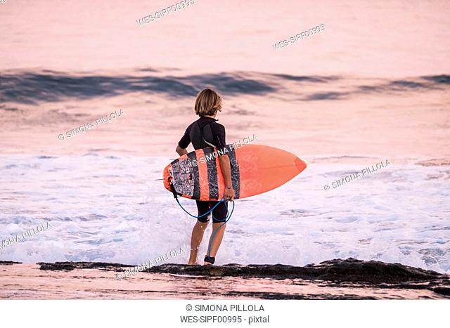Spain, Tenerife, boy carrying surfboard at the sea