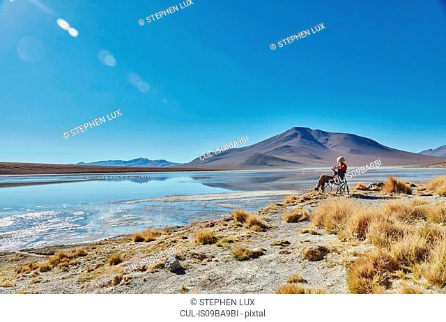 Woman sitting in camping chair, looking at view, Salar de Chalviri, Chalviri, Oruro, Bolivia, South America