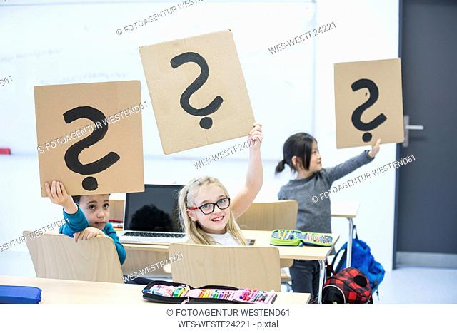 Pupils with laptop in class holding up cardboards with question marks