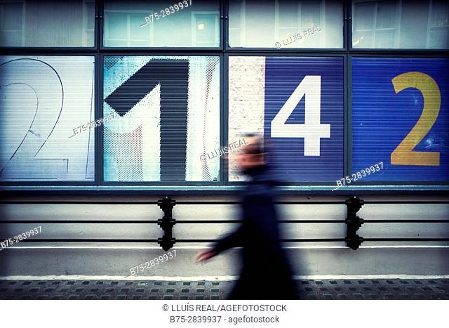 un hombre andando en movimiento irreconocile, al fondo una fachada con numeros 2-1-4-2. London, UK, Europa