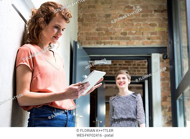 Woman using tablet with colleague in background