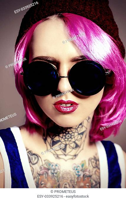 Close-up portrait of a modern girl with bright crimson hair and round sunglasses. Tattoo. Hair coloring. Optics style