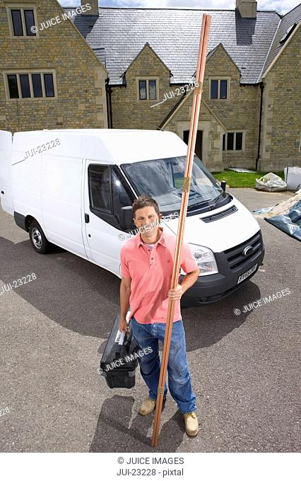 Smiling man holding toolbox and copper pipes near work van