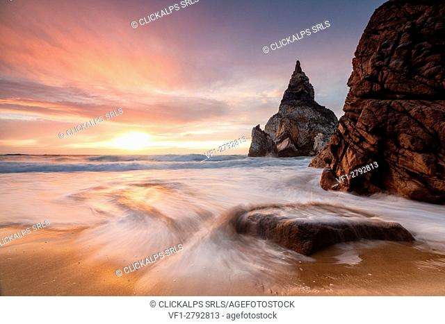 Golden reflections of the cliffs on Praia da Ursa beach bathed by ocean at sunset Cabo da Roca Colares Sintra Portugal Europe
