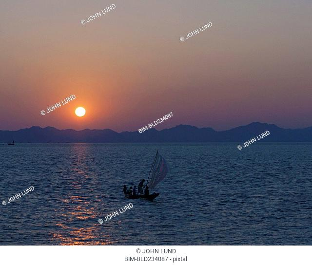 People in sailboat on ocean at sunset