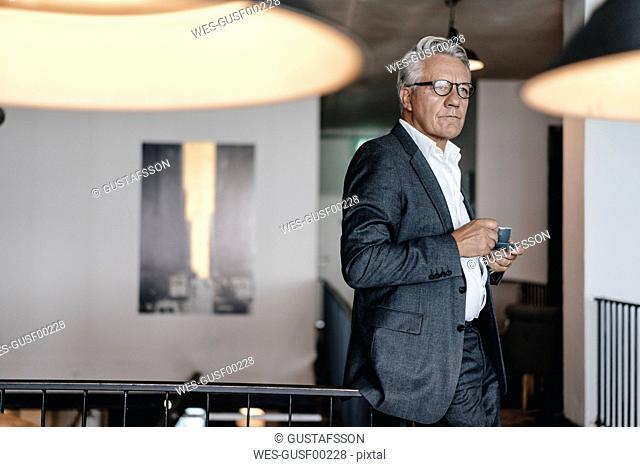 Senior businessman drinking coffee, looking worried