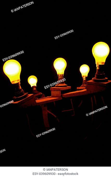 Wooden light fixture holding 5 tungsten light bulbs