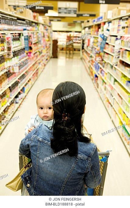 Asian mother shopping with baby in grocery store
