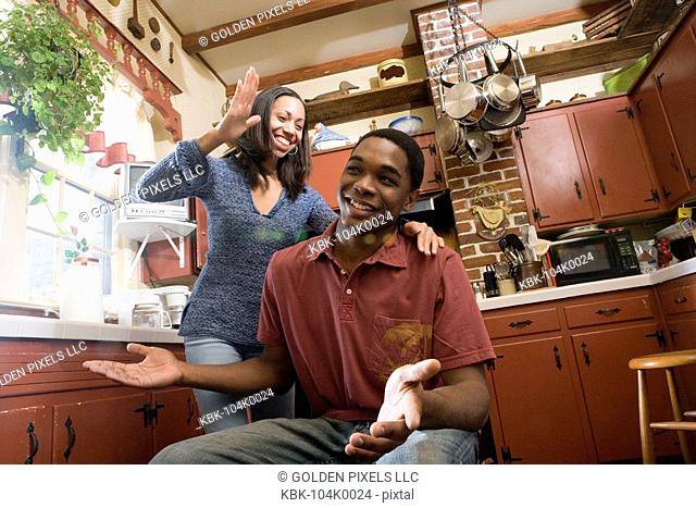 African American brother and sister laughing in kitchen