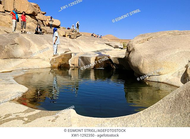 Tourists at Guelta Afilal, waterhole in the desert of the Hoggar, Ahaggar Mountains, Wilaya Tamanrasset, Algeria, Sahara, North Africa
