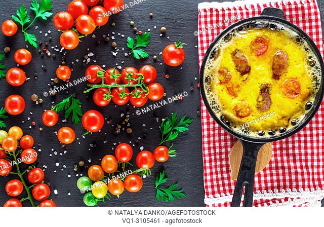 fried omelette with sausages and chicken eggs in a round cast-iron pot and ripe red cherry tomatoes on a black background, top view