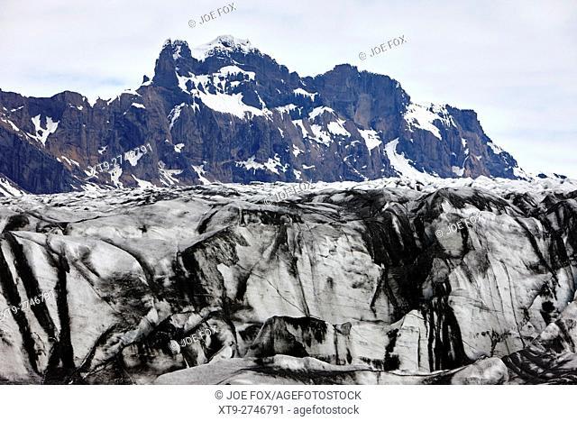ash covered Skaftafell glacier snow covered mountains Vatnajokull national park in Iceland