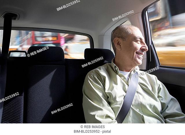 Smiling Hispanic man riding in car
