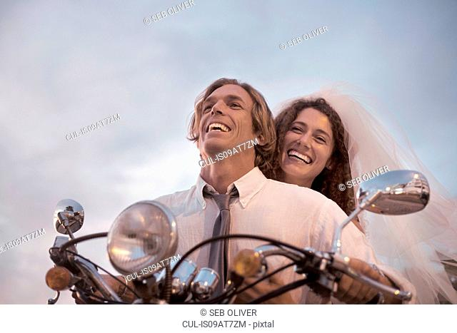 Bride and groom riding motorcycle against sunset