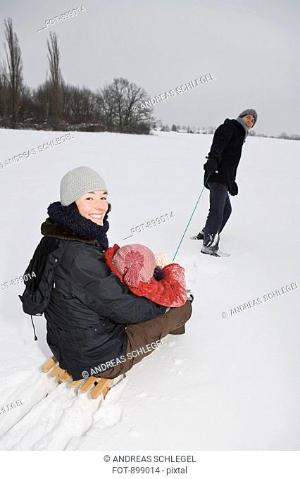 A man pulling a sled with his wife and daughter on it