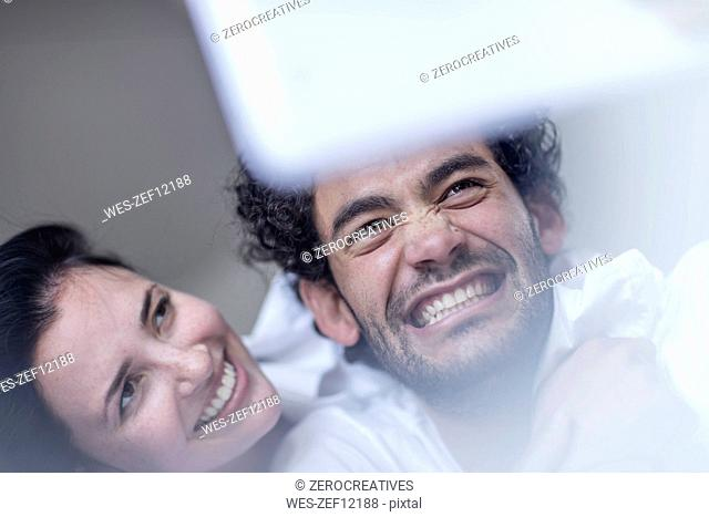Smiling young couple together in bed with a tablet