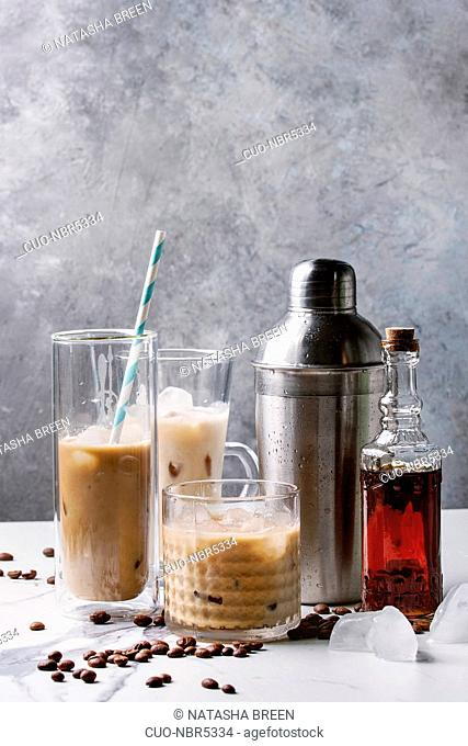 Iced coffee cocktail or frappe with ice cubes and cream in different glasses with silver shaker, bottle of rum, coffee beans around on white marble table with...