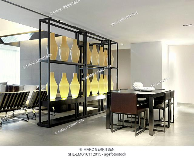 Vases arranged on shelves between living and dining area
