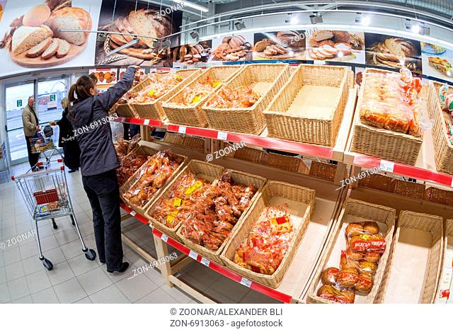 SAMARA, RUSSIA - OCTOBER 5, 2014: Young woman choosing fresh bakery products at shopping in supermarket store Magnit. Russia's largest retaile